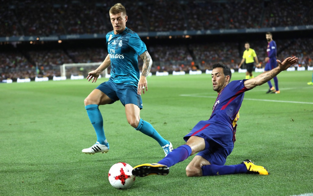 Sergio Busquets klärt mit der Grätsche vor Toni Kroos im Supercopa-Hinspiel FC Barcelona - Real Madrid in der Saison 2017/18.