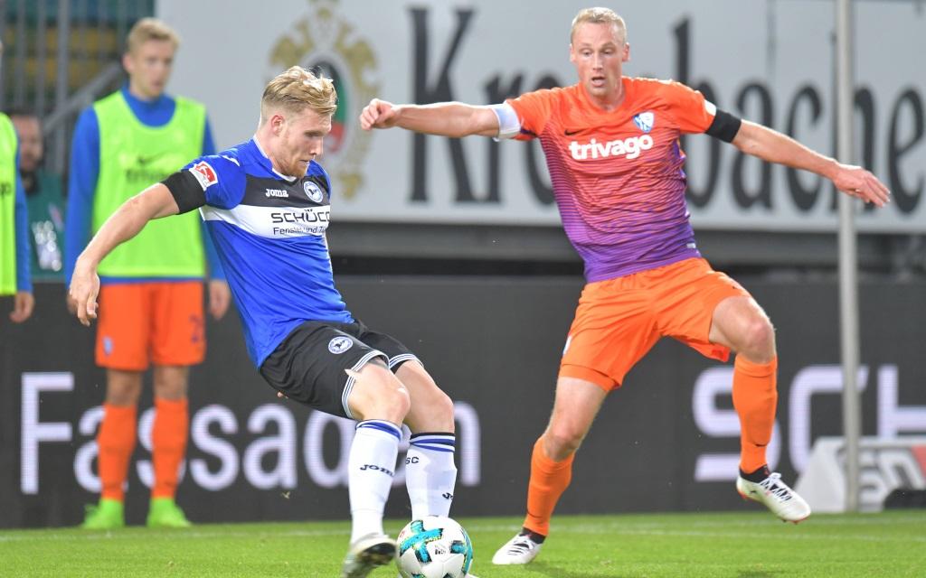 Andreas Voglsammer beim Schussversucht vor Felix Bastians im Spiel Arminia Bielefeld - VfL Bochum.