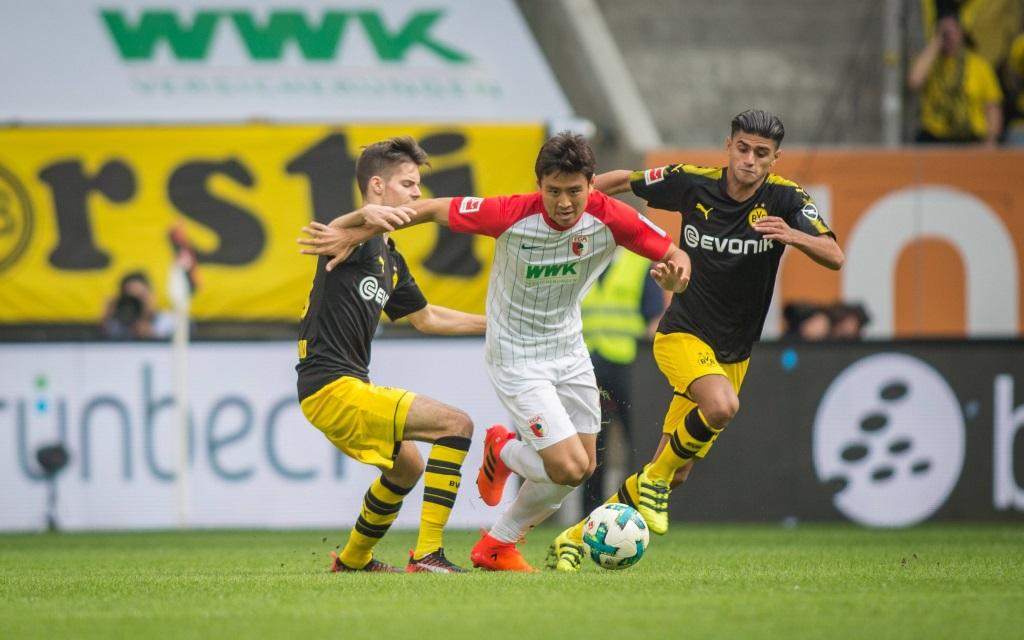 Ja-Cheol Koo (FC Augsburg) im Zweikampf mit den Dortmundern Julian Weigl und Mo Dahoud.