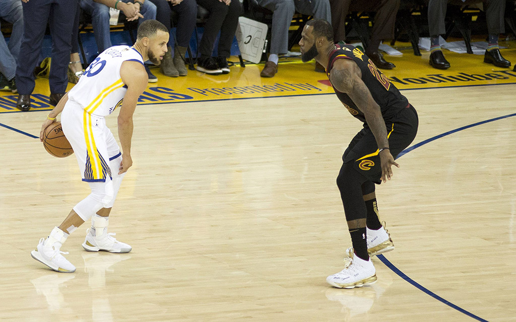 NBA-Finals: Warriors-Star Curry (l.) mit dem Ball gegen Clevelands James (r.)
