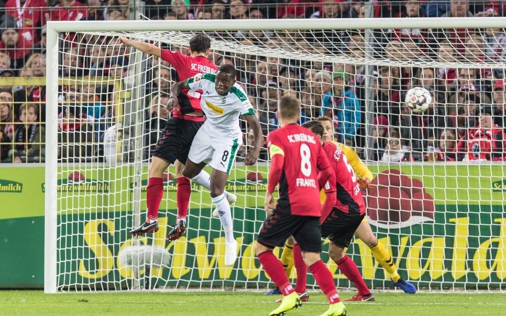 Kopfballduell zwischen Nicolas Hoefler (SC Freiburg 27) und Denis Zakaria (Borussia Moenchengladbach, 8) vor Freiburger Tor