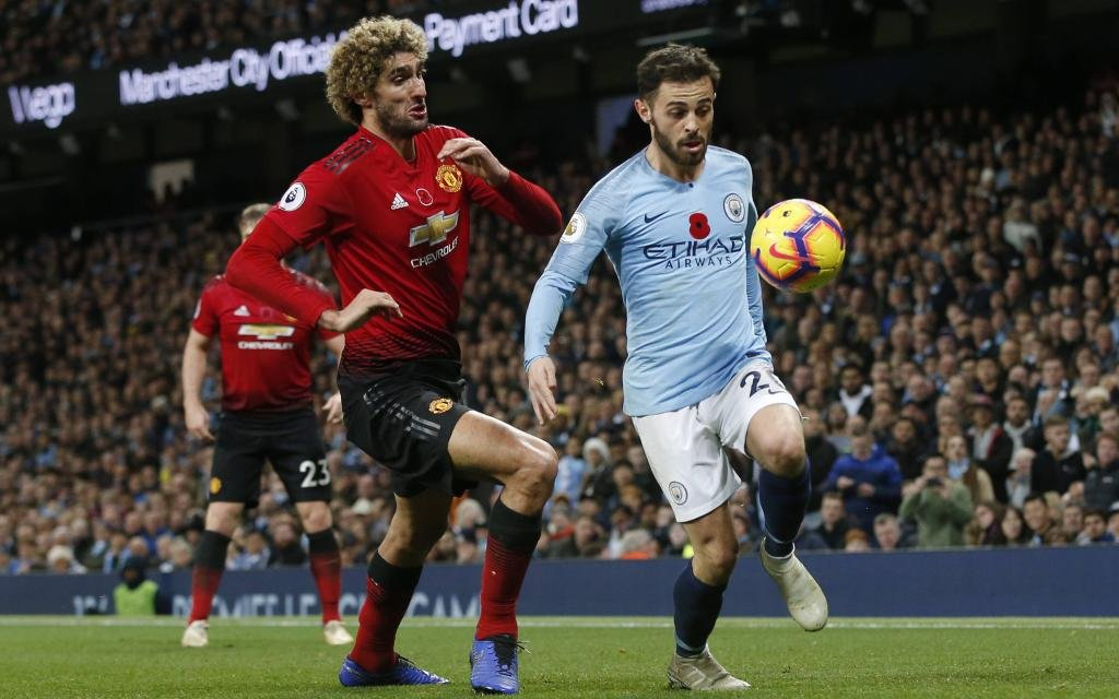 Bernardo Silva of Manchester City chased by Marouane Fellaini of Manchester United ManU during the Premier League match at the Etihad Stadium,