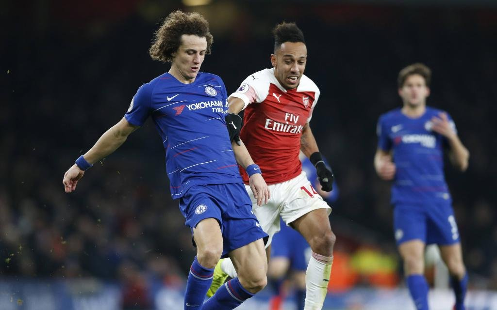 Chelsea s David Luiz (L) is challenged by Arsenal s Pierre-Emerick Aubameyang during the 23th round English Premier League match between Arsenal and Chelsea at the Emirates Stadium in London