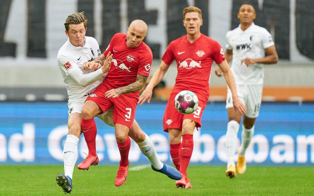 Michael Gregoritsch im Zweikampf mit Angelino. Dahinter Marcel Halstenberg im Spiel Augsburg - Leipzig Saison 2020/2021